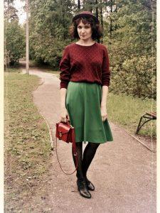 Молодая девушка в зеленой юбке и бордовом свитере