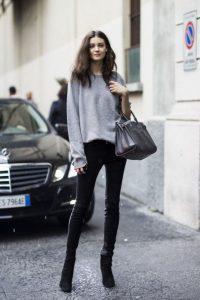 Девушка в черных брюках, сером свитере и с сумкой на руке