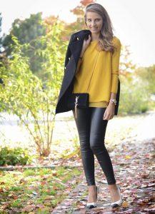Брюки черного цвета, темное пальто и желтая кофта