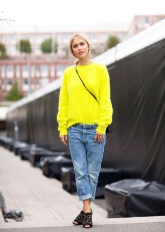 Девушка блондинка в джинсах светлого оттенка и в яркой желтой кофте