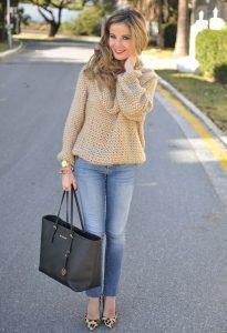 Красивая девушка, стоящая на дороге, в светлых джинсах, красивом свитере и с сумкой черного цвета в руках