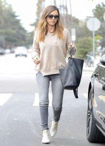 Девушка около машины в серых джинсах и светло коричневом свитере