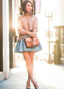 Девушка в короткой джинсовой юбке и свитере