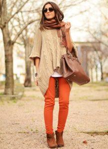 Девушка в оранжевых брюках и длинном свитере