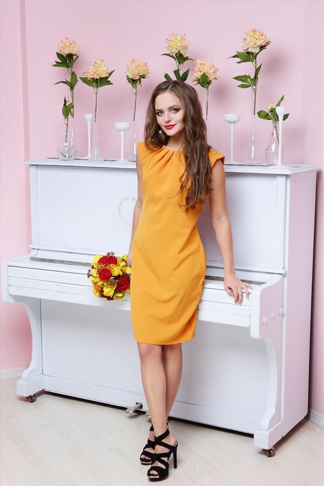 Девушка около белого пианино в горчичном платье