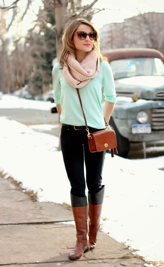 Девушка на улице зимой в кофте, шарфе, с сумкой и высоких сапогах коричневого цвета
