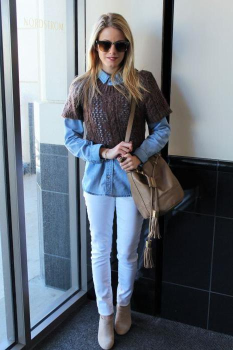 Девушка в белых брюках, синей блузке, коричневом свитере и с бежевой сумкой