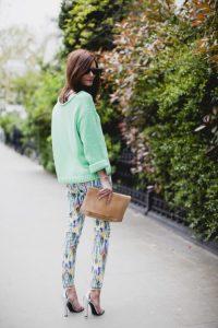 Девушка летом в легких брюках, свитере и с клатчем в руке