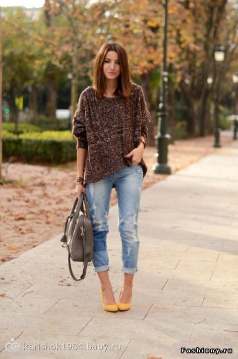 Модель в джинсах, туфлях, свитере с сумкой в руках