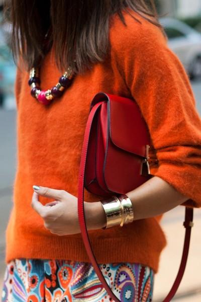 Оранжевый свитер, красная сумка, золотой браслет, бусы