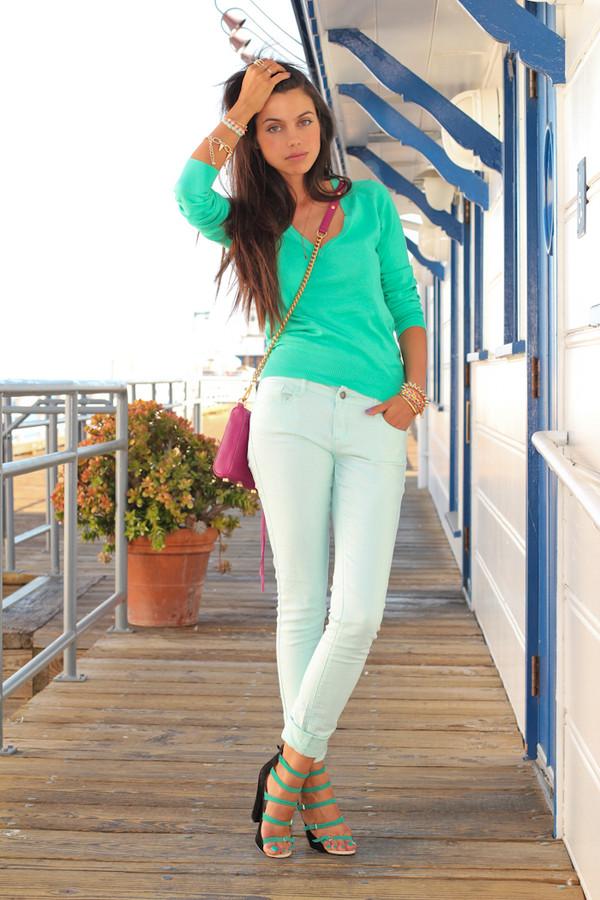 Девушка на террасе в белых брюках и бирюзовой кофте