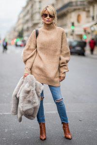 Девушка в бежевом длинном свитере, в джинсах с разрезом на колене, в коричневых ботинках и в солнцезащитных очках