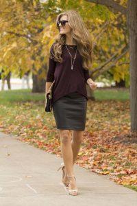 Девушка в осеннем парке в коричневом свитере и темной юбке