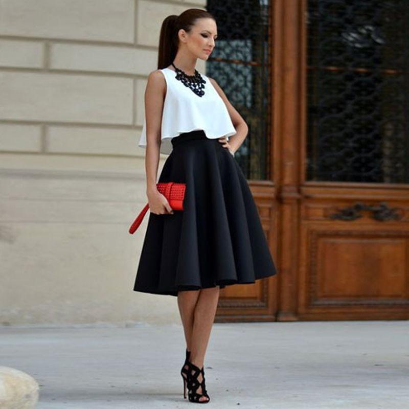 Модель в черной юбке и белой блузке с клатчем красного цвета в руках