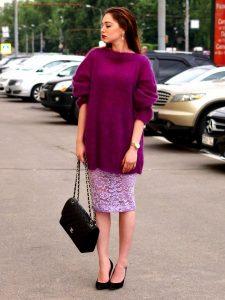 Девушка в длинном фиолетовом свитере и юбке с сумкой черного цвета
