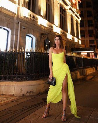 Модель позирующая на улице в шикарном желтом длинном платье
