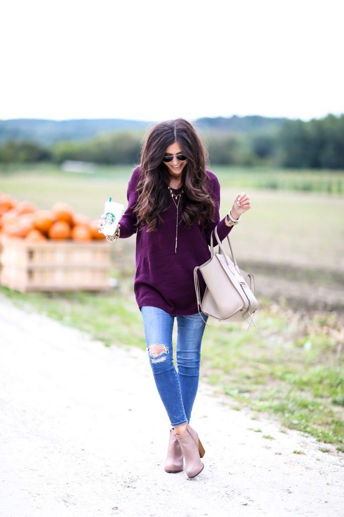 Девушка рядом с тыквами в фиолетовом удлиненном свитере и в джинсах
