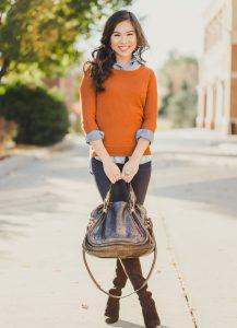 Модель в оранжевом свитере, брюках, высоких сапогах и с металлической сумкой в руках