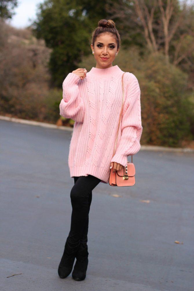 Девушка на улице в розовм длинном свитере и с сумкой на плече