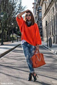 Модель, позирующая на улице, в джинсах с дырками, оранжевой сумкой и свитере