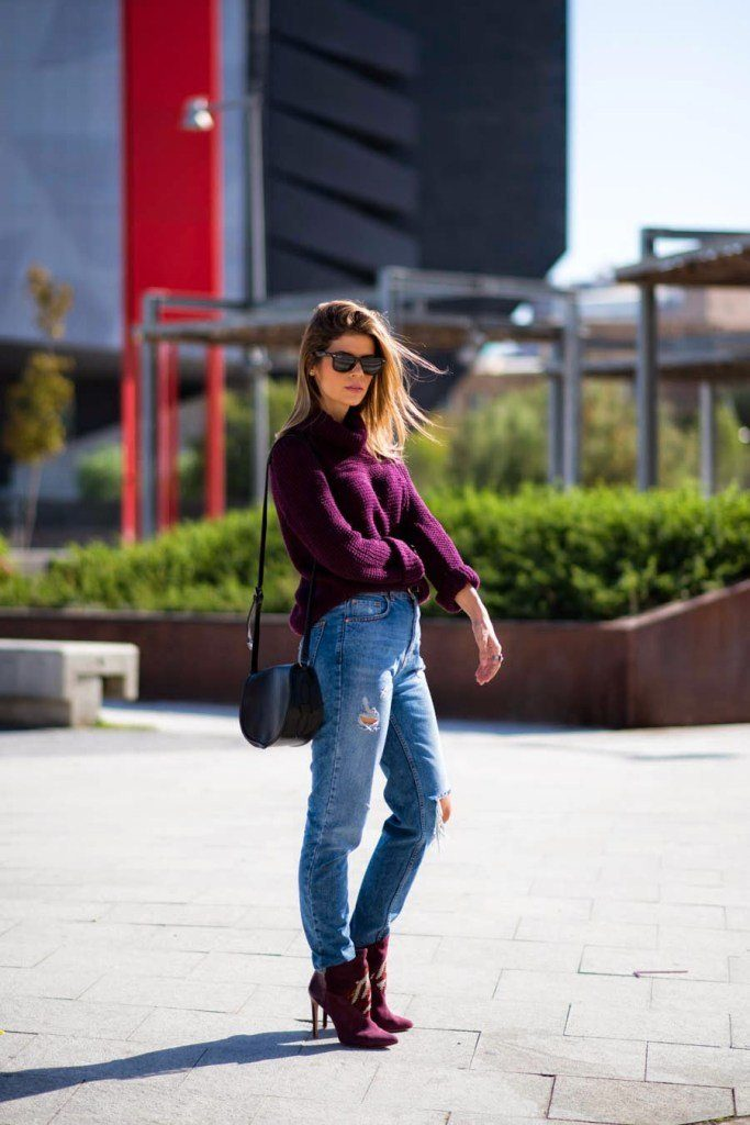Девушка около лестнице в джинсах, свитере, очках и с сумкой