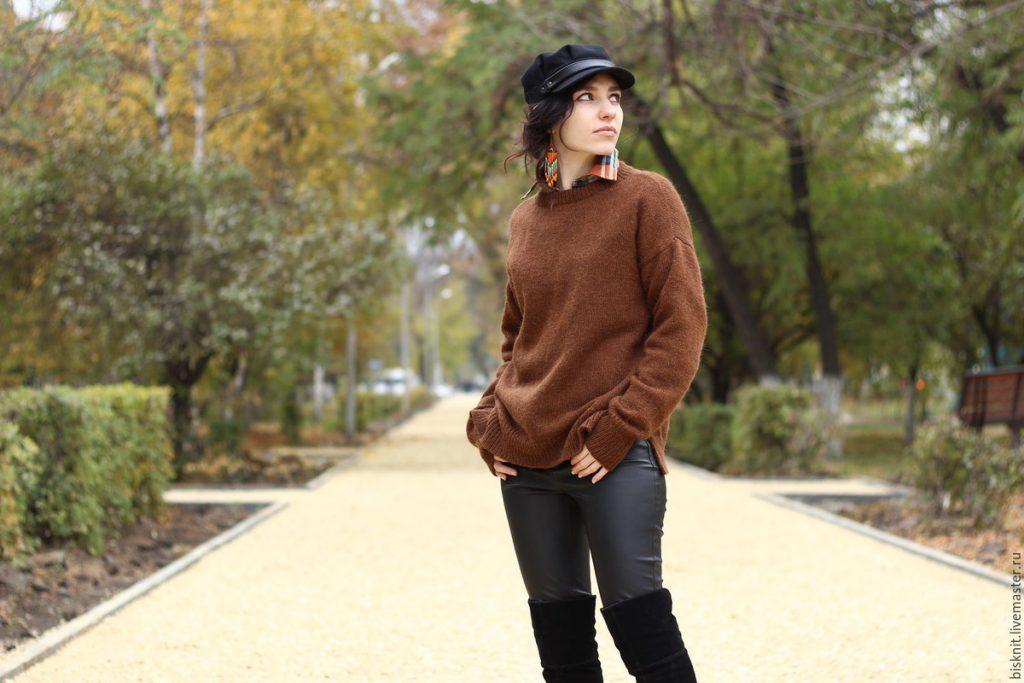 Позирующая девушка в кепке, джинсах, ботфортах и коричневом свитере