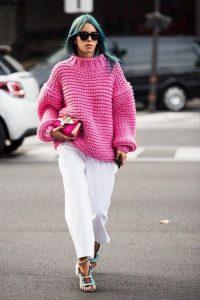 Девушка, идущая по парковке, в ярко-розовом свитере, белых брюках