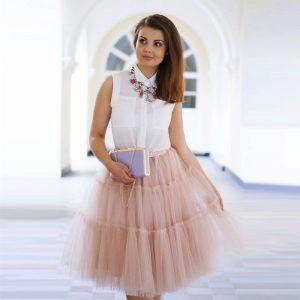 Девушка в пышной юбке кораллового цвета и белой блузке