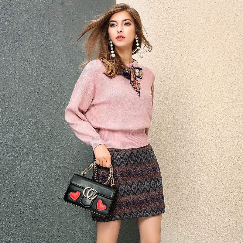 Модель в юбке и свитере и с сумкой в руках