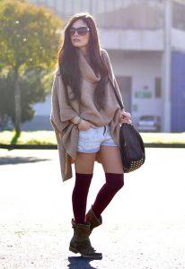 Модель в коричневом свитере, светлых шортах и коричневых ботинках