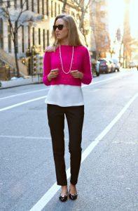 Девушка в ярко-розовом укороченном свитере, темных брюках и в белой блузке