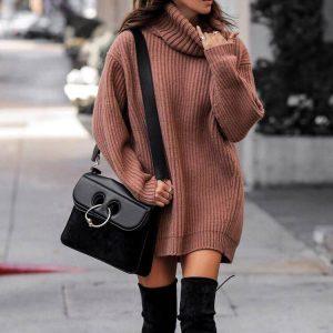 Девушка в коричневом длинном свитере, высоких сапогах и с черной сумкой на плече