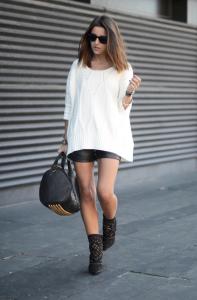 Белый свитер, кожаные короткие шорты, черные ботинки и сумка
