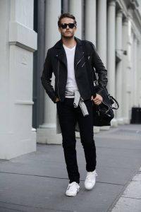 Парень, идущий по улице в черной куртке, белой футболке и с сумкой на плече