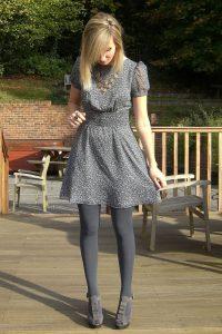 Девушка в красивом сером платье и таких же колготках на улице