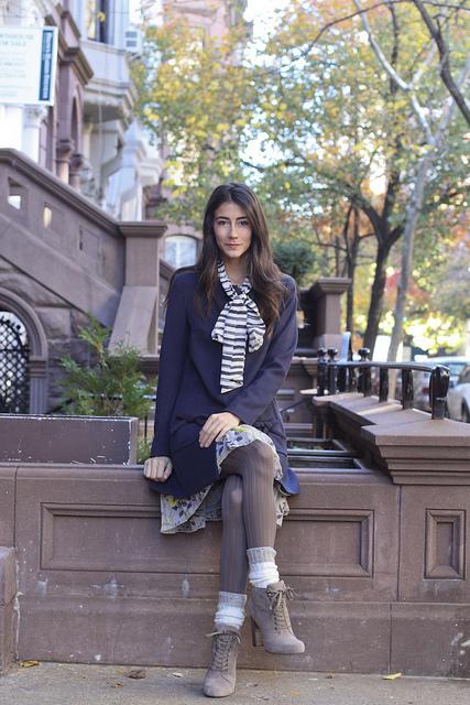 Модель в пальто синего цвета, колготках серого оттенка, шарфе