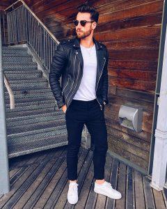 Мужчина модель в черных джинсах, куртке и белой футболке