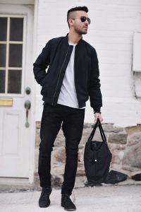 Мужчина в черной куртке, белой футболке, черных брюках и с сумкой в руке