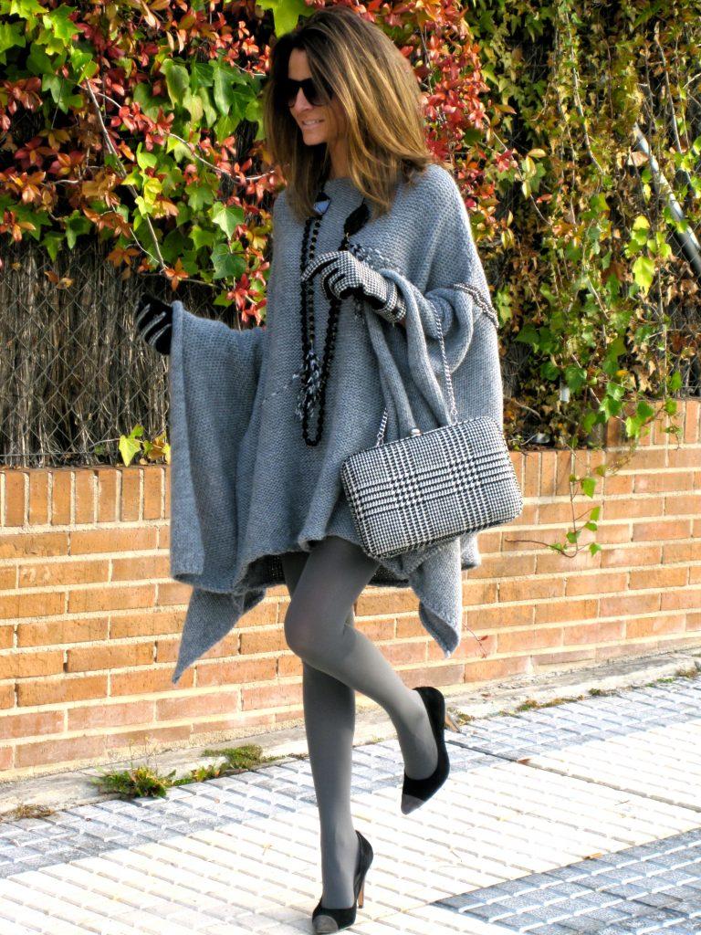 Девушка в пончо серого цвета, с серой сумкой в руке и серых колготках