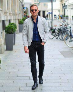 Мужчина в темных джинсах, светлой куртке бомбере и в синей рубашке