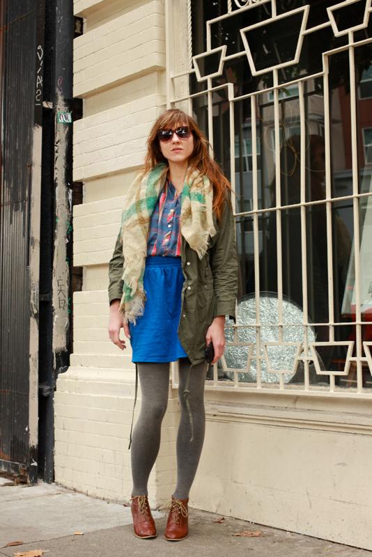 Оригинальный повседневный лук, состоящий из куртки парки, синей юбке и серых колгот