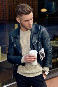 Парень модель в свитере, куртке, с кофем в руках и газетой подмышкой