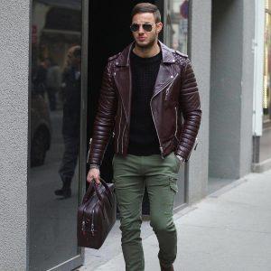 Мужчина, идущий по улице в бордовой куртке косухе, в зеленых брюках и с сумкой в руке
