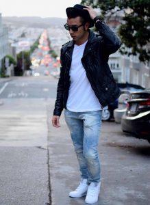 Мужчина на улице в кожаной куртке, белой футболке, светло-голубых джинсах