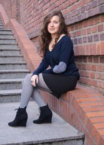 Девушка, сидящая на бордюре, в серых колготах, черной юбке и синем свитере