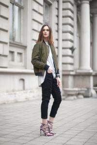 Модель в черных джинсах, удлиненной блузке, болотной куртке