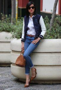 Девушка модель с коричневой сумкой в руках, синих джинсах, белой блузке и в куртке