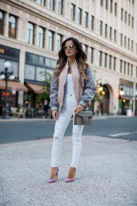 Девушка в белых брюках, белом топе, в серой куртке и с сумкой на плече