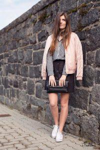 Девушка в юбке, с розовой курткой на плечах
