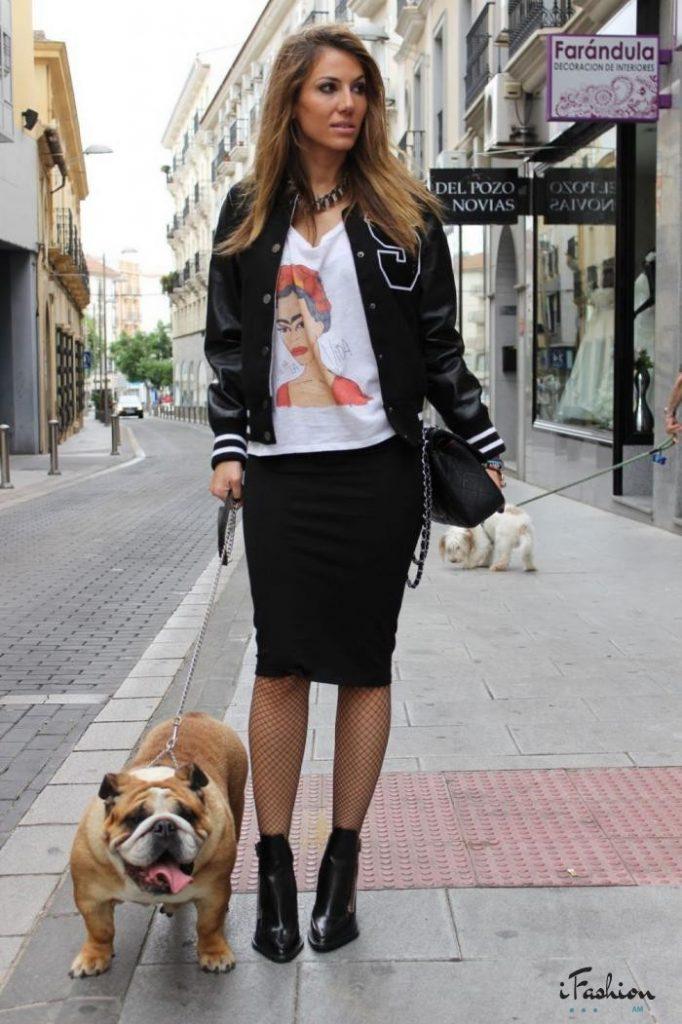 Девушка в черном бомбере в белой футболке, в юбке карандаш и с собакой на поводке